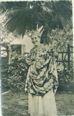 Tanlistwa, photographie en noir et blanc d'une jeune martiniquaise en costume local (jupon blanc, robe à motif, coiffe madras à trois pointe, collier et boucle d'oreilles) debout dans un jardin, souriante