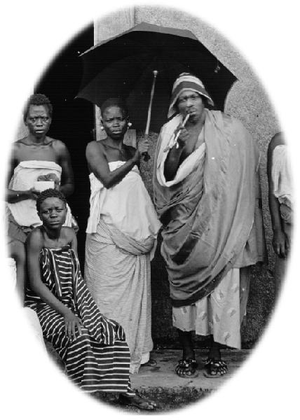 tanlista, détail d'une photo en noir et blanc de Béhanzin en tenue officielle (drapé d'un grand tissus, pipe longue et coiffe couvrant les oreilles, installé sous un parapluie cérémoniel)