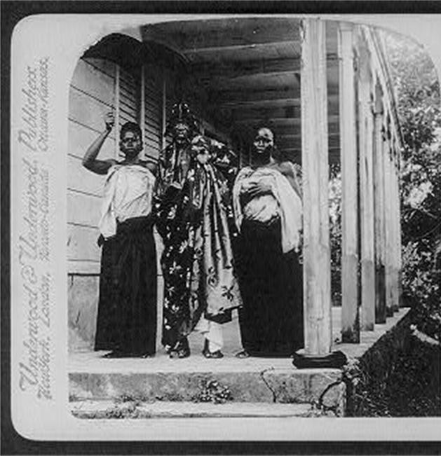 tanlista, extrait d'une carte postale en noir et banc de Béhanzin en tenue officielle (drapé d'un grand tissus, pipe longue et coiffe couvrant les oreilles, installé sous un parapluie cérémoniel) entourée de deux épouses. Ils sont sous la véranda de la villa les bosquets.