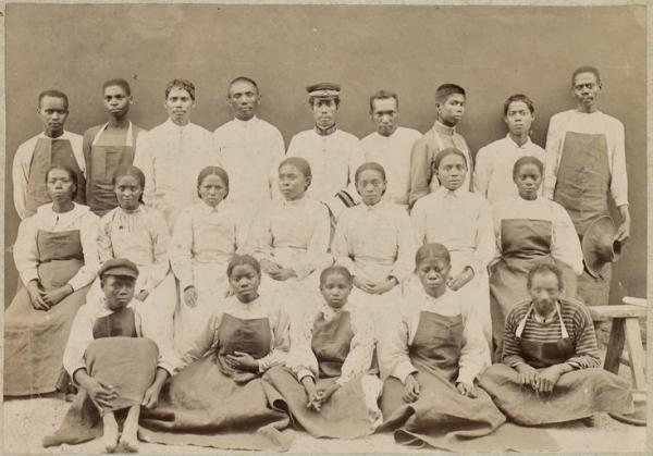 Tanlista, photographie en noir et blanc représentant sur 3 rangées des infirmiers et infirmières noires posant contre un mur, premier rang assis au sol, le second sur un banc, le dernier debout. Ils portent un uniformes blancs, robes pour les femmes, parfois surmonté d'un tablier sombre